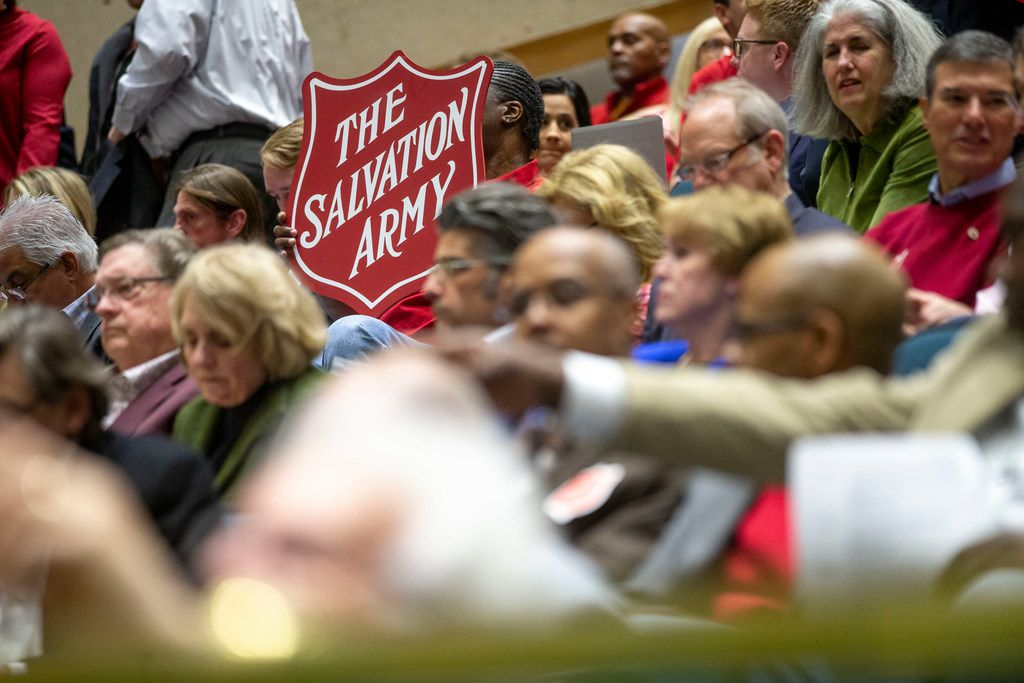 A member of the audience holds the Salvation Army's logo during a City Plan Commission meeting at Dallas City Hall on Thursday, March 7, 2019. (Shaban Athuman/The Dallas Morning News)