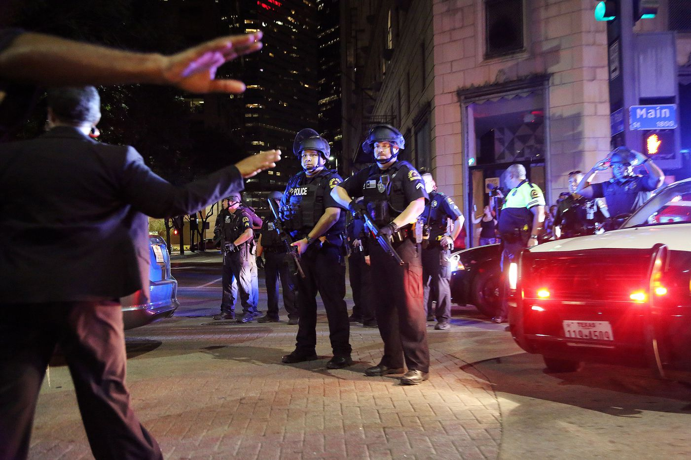 """Organizers attempt to move protesters out of the street while Dallas police officers get out of cars at the corner of Main Street and St. Paul Street during a protest held by the Next Generation Action Network in downtown Dallas Thursday September 22, 2016. The protest, which started at the Main Street Garden Park and is called """"Enough is Enough,"""" is in reaction to recent shooting by police in Tulsa and Charlotte. (Andy Jacobsohn/The Dallas Morning News)"""