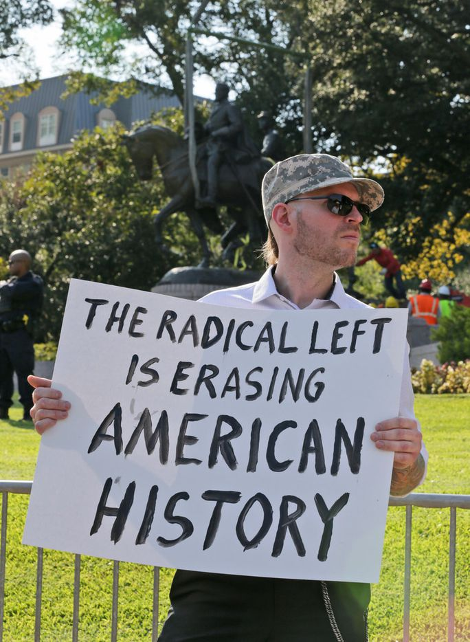 Frank Darvo holds a sign as workers prepare for the removal of a statue of Robert E. Lee at a public park in Dallas, Thursday, Sept. 14, 2017. (AP Photo/LM Otero)
