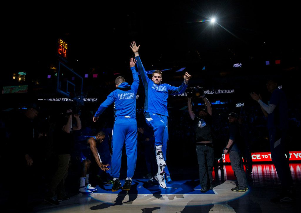 Dallas Mavericks guard Luka Doncic (77) high-fives guard J.J. Barea (5) as they are introduced before an NBA game between the Dallas Mavericks and the Phoenix Suns on Tuesday, January 28, 2020 at the American Airlines Center in Dallas.