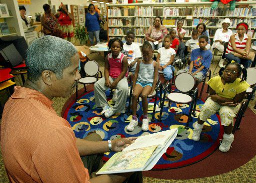 ORG XMIT: *S0410102454* 9/4/04 -- #75625-----Former Dallas Cowboy Everson Walls  reads to a group of children at the Martin Luther King Jr. Library Saturday September 04, 2004. The reading was part of the Second Annual Tulisoma South Dallas Book Fair and Arts Festival.  08192005xGUIDE