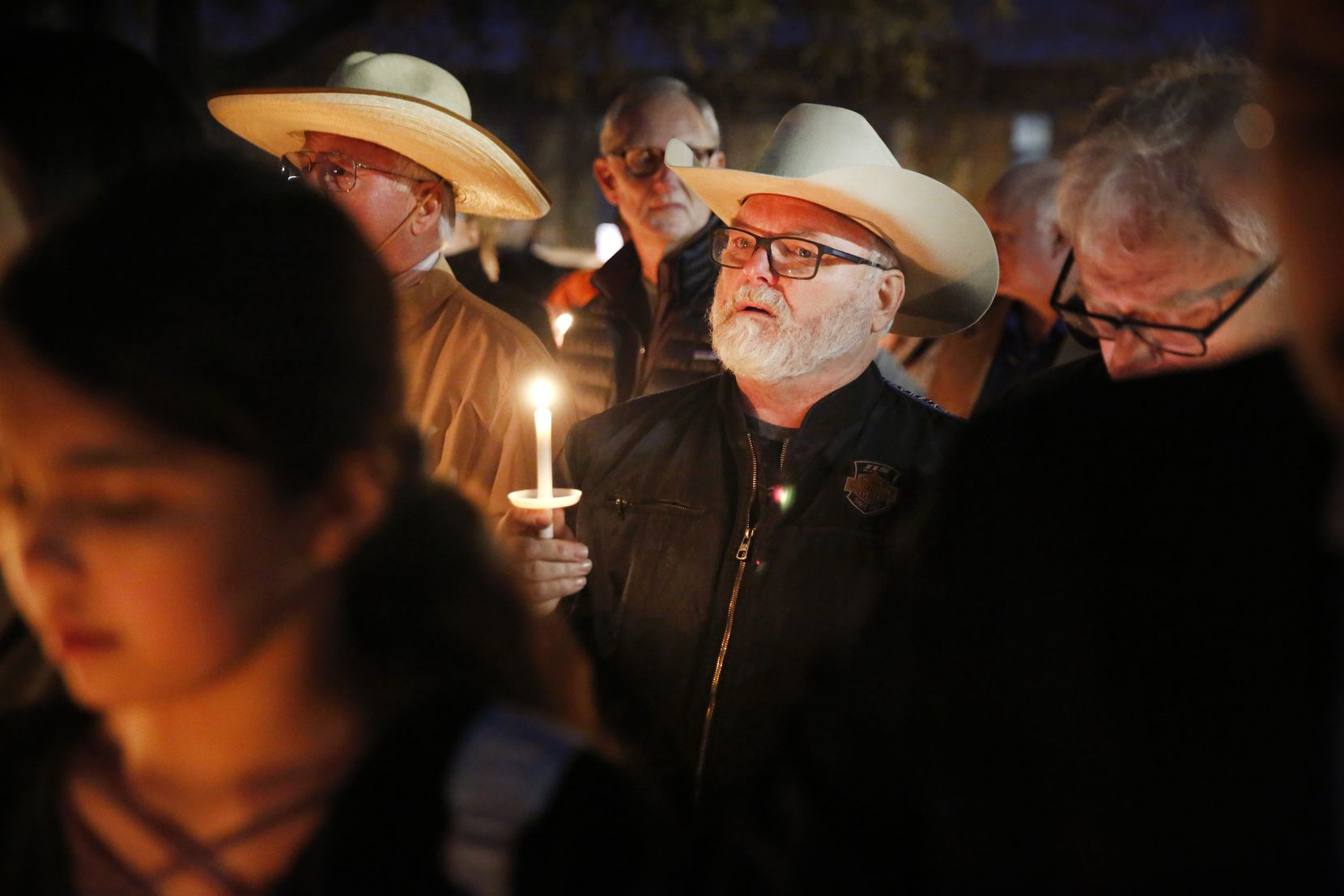 Stephen Willeford, the man who confronted and exchanged gunfire with the Sutherland Springs church shooter in 2017 (center) joined church and community members gathered outside the West Freeway Church of Christ in Fort Worth for a candlelight vigil Monday evening.