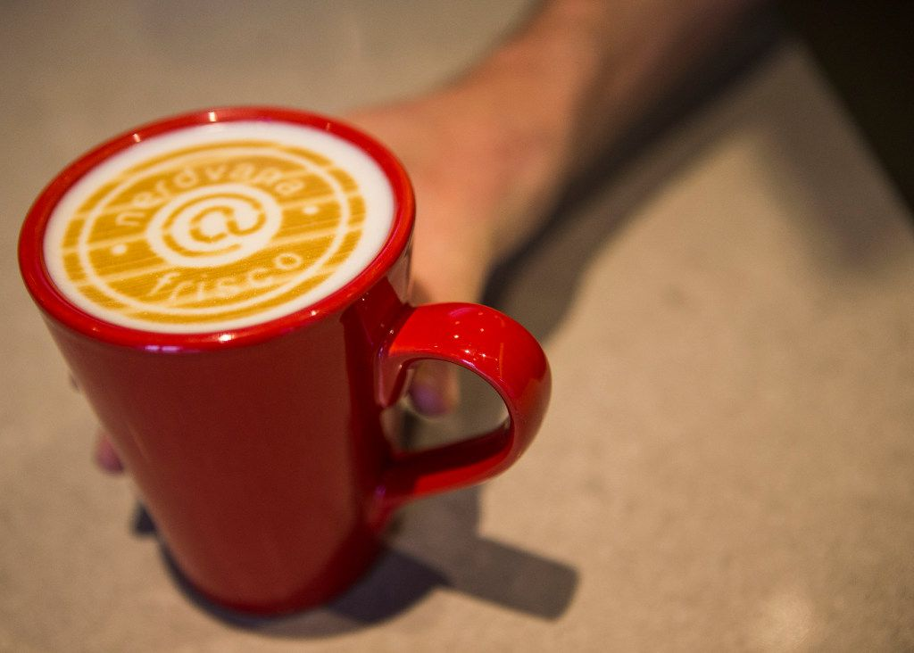 Collin Mizell shows off a cup of coffee with a logo printed on the milk at Nerdvana Coffee in downtown Frisco.