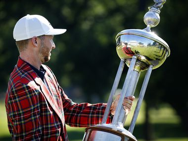 On the 18th green, PGA Tour golfer Daniel Berger looks at himself reflected in the winning Leonard Trophy after defeating Collin Morikawa in a one hole playoff in the final round of the Charles Schwab Challenge at the Colonial Country Club in Fort Worth, Sunday, June 14, 2020. The Challenge is the first tour event since the COVID-19 pandemic began. (Tom Fox/The Dallas Morning News)