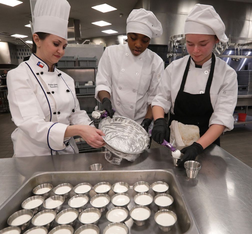 Executive chef Annette Greenslade, left, helps 17-year-old Tamaisha Ajaero and 16-year-old Evan Maine prepare marshmallow dipping sauce at Allen High School's Blu Community Bistro.