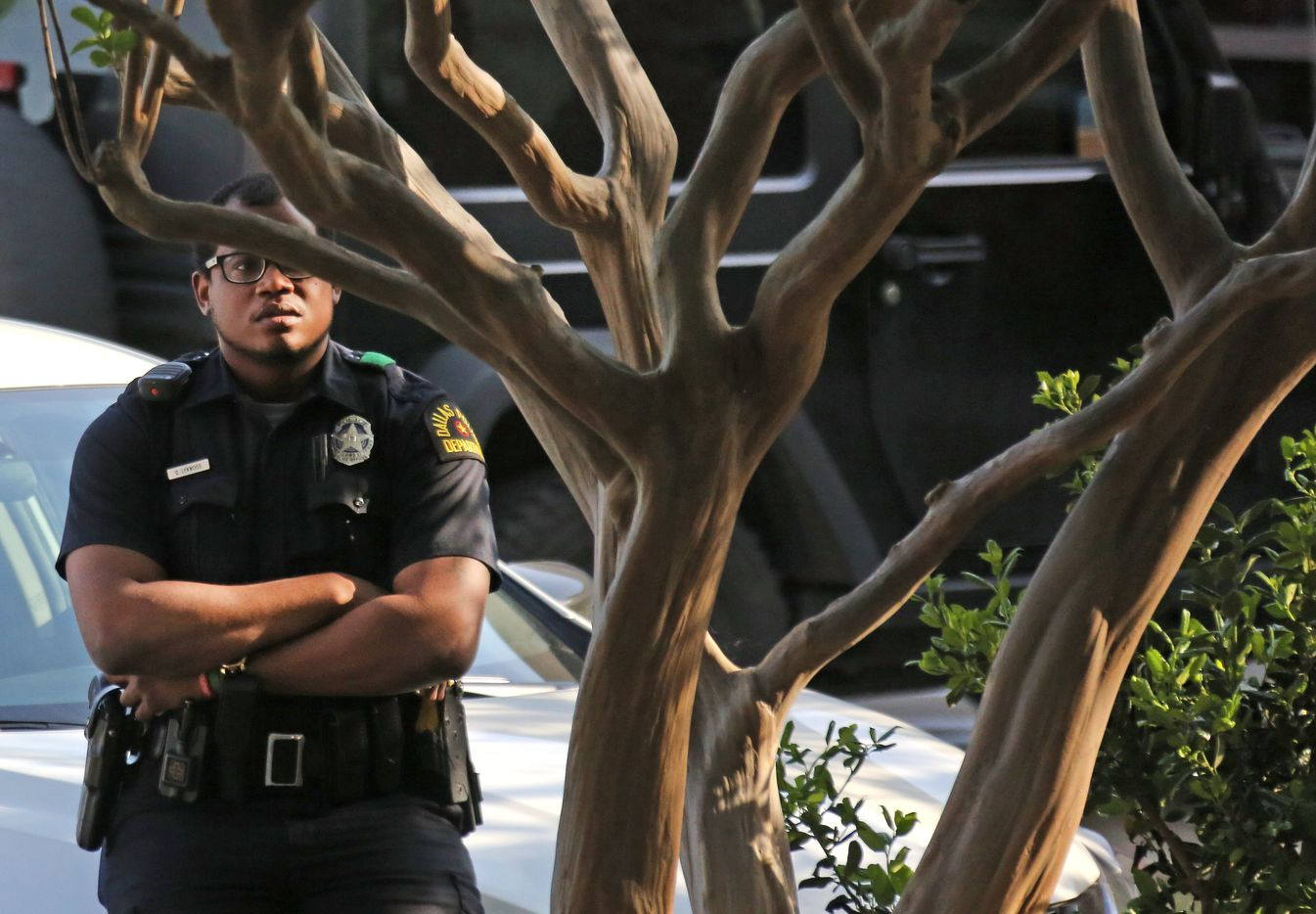 A Dallas police officer watches from a distance at the emergency room entrance at Presbyterian Hospital in Dallas. Two Dallas policemen were reportedly shot at a nearby Home Depot and reportedly were transported to the Dallas hospital on April 24, 2018.