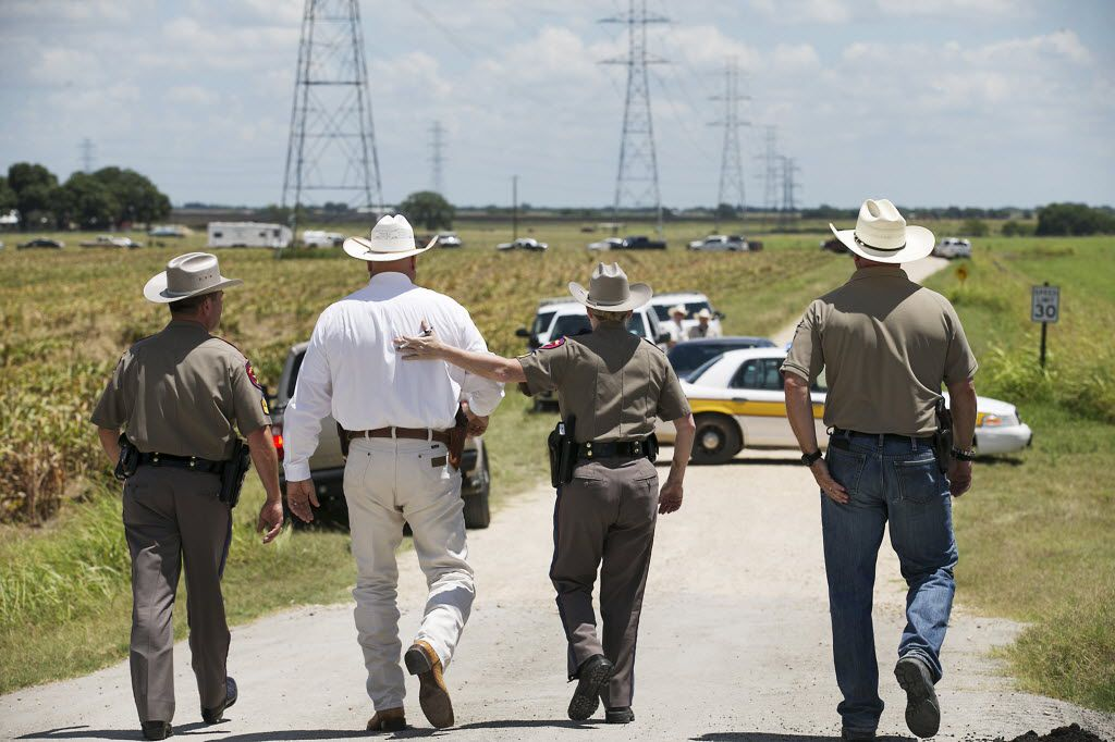 Texas DPS Trooper Robbie Barrera, center right, puts her arm around Caldwell County Sheriff Daniel Law as he arrives at the scene of a hot air balloon crash that killed 16 people near Lockhart, Texas, on Saturday, July 30, 2016. (Ralph Barrera/Austin American-Statesman/TNS)