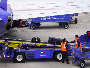 Baggage handlers unload a Southwest Airlines flight at Dallas Love Field on Thursday, Jan. 7, 2021, in Dallas. (Smiley N. Pool/The Dallas Morning News)