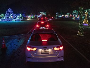 A line of vehicles slowly move through the Christmas Safari section of the Prairie Lights at Lynn Creek Park in Grand Prairie, on Saturday, Nov. 28, 2020. Families are treated to four million lights along a two mile path with hundreds of new displays this year.