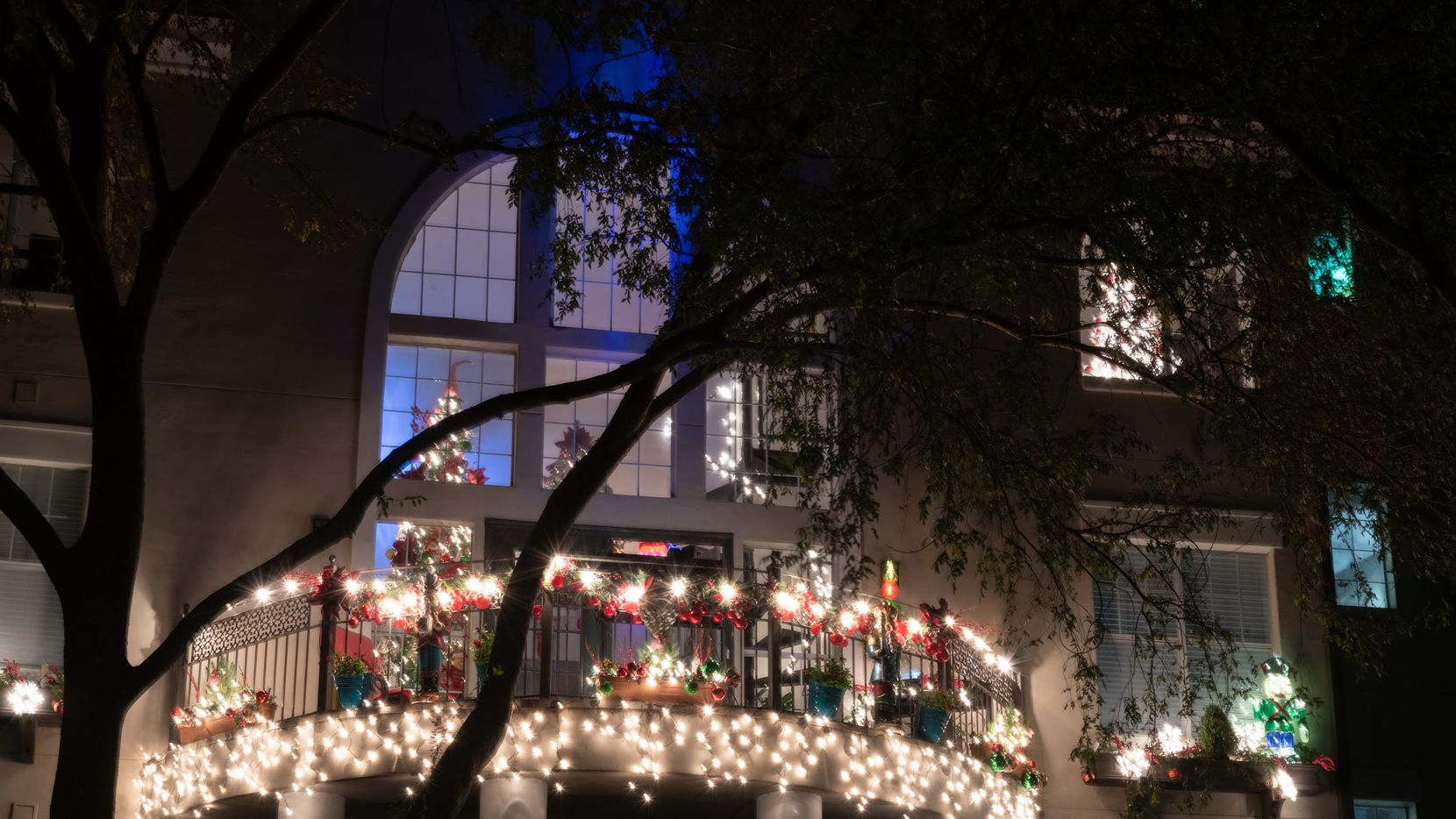 """On weekends, a machine shoots snow from the balcony of Harley Gonzales' Las Colinas penthouse, which he has transformed into the """"Miracle on West Fork"""" as he tries to bring a little holiday cheer to passersby."""