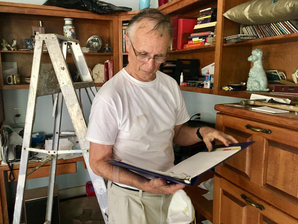 Arthur Storey, the former head of the Harris County Flood Control District, flips through one of his most cherished possessions -- a ballroom dance step guide from when he and his wife met -- at his flood-damaged home in Memorial Drive Acres in Houston on Sept. 9, 2017. (Naomi Martin/ Staff)