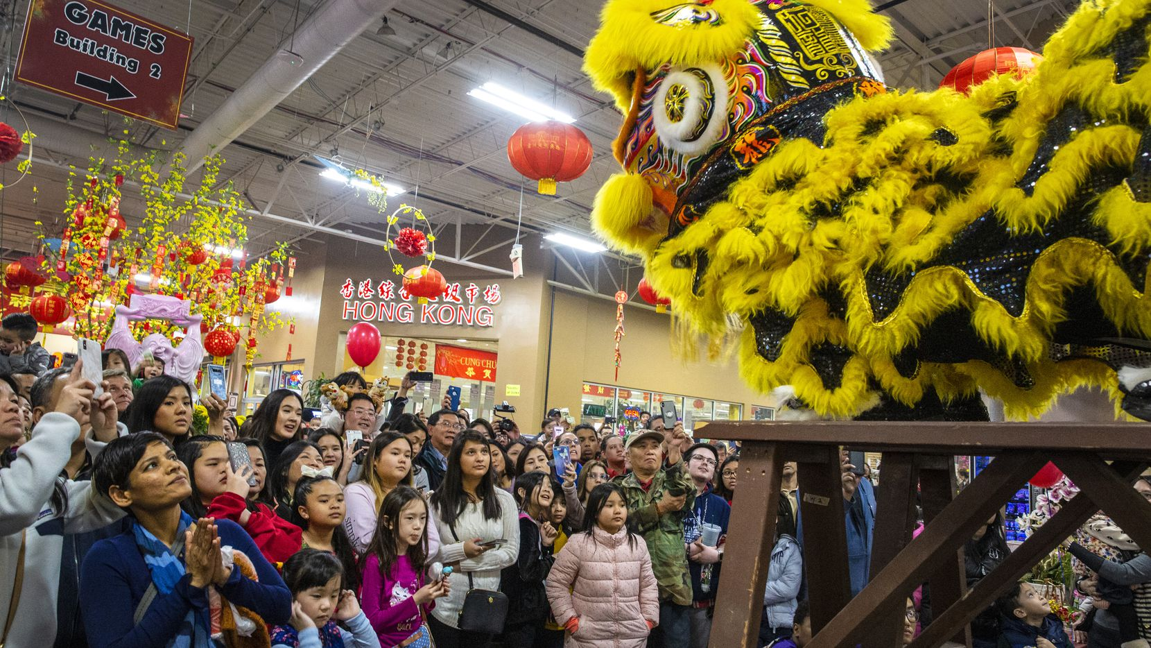 Spectators watch as people with the Jiu Long Sports Association put on a performance during Lunar New Year Festival at Asia Times Square in Grand Prairie, Texas on Jan. 26, 2019. The Jiu Long Sports Association aims to share Asian culture.