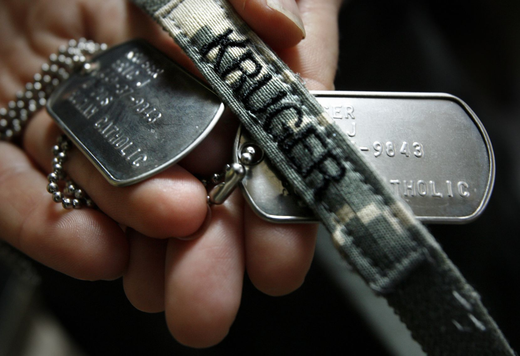 Kristy Kruger holds her brother Lt. Col. Eric Kruger's dog tags and helmet band after he died in Iraq on November 2006.
