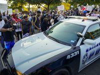 A group of demonstrators yells at a passing Dallas police vehicle at Lake Cliff Park on Tuesday.