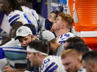 Dallas Cowboys quarterback Andy Dalton watches from the bench with offensive coordinator coach Kellen Moore during the fourth quarter of a loss to the Arizona Cardinals in an NFL football game at AT&T Stadium on Monday, Oct. 19, 2020, in Arlington.