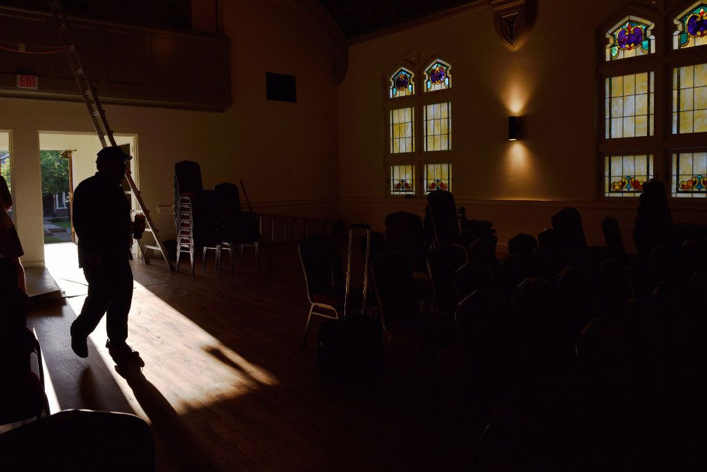 The shadow of a worker is cast on the floor of the Arts Mission Oak Cliff, formerly the Winnetka Congregational Church, during preparation for a show.