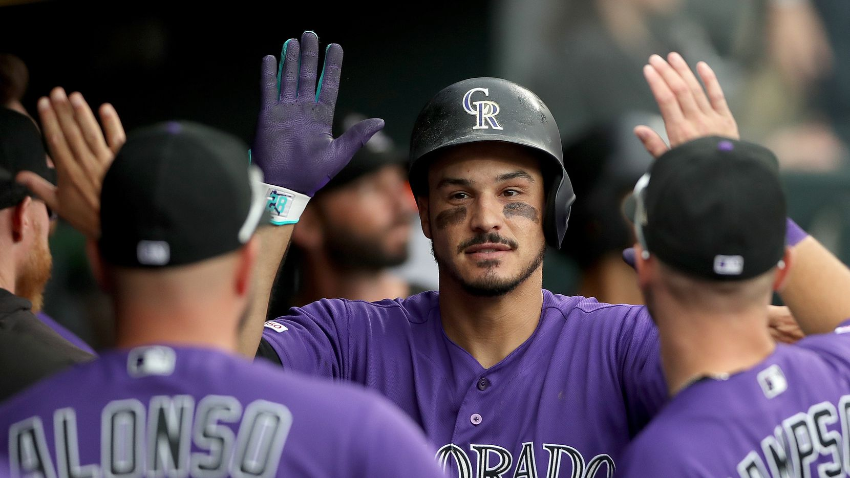 DENVER, COLORADO - AUGUST 04: Nolan Arenado #28 of the Colorado Rockies celebrates in the dugout after hitting a home run in the fifth inning against the San Francisco Giants at Coors Field on August 04, 2019 in Denver, Colorado.