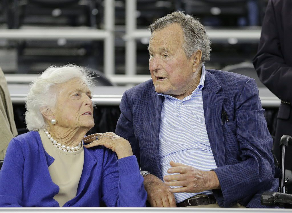 In a file photo from 2015, former President George H.W. Bush and his wife, Barbara Bush, appear at the NCAA basketball tournament in Houston. The Treasury will issue coins to honor the couple, who died in 2018.