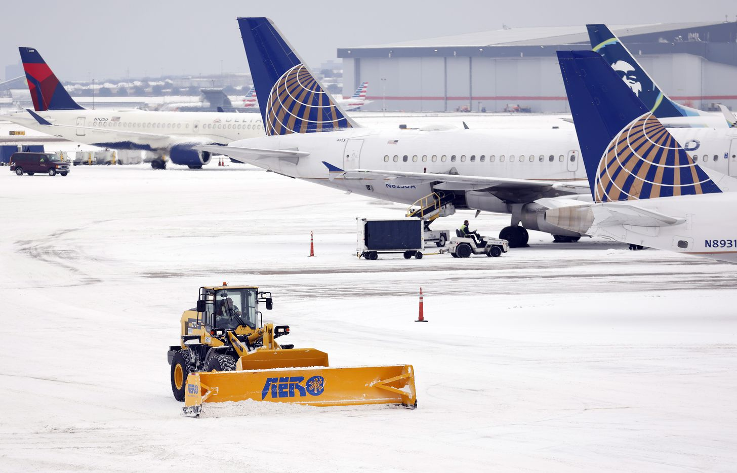 Crews use plows to clear snow from the Terminal B tarmac at Dallas-Fort Worth International Airport, Wednesday, February 17, 2021. Another round of snow fell overnight at the airport.