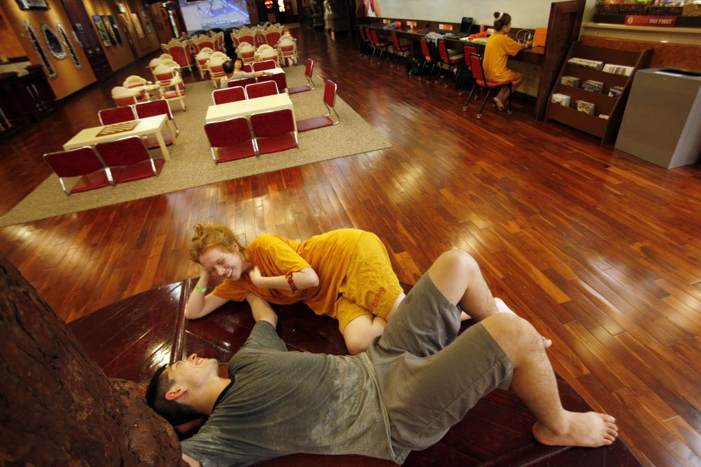 Madison Gilbert, 23, and Salam Matsuda, 22, relax between a restaurant and communal space inside King Spa, on Wednesday, Oct. 06, 2015 in Dallas.