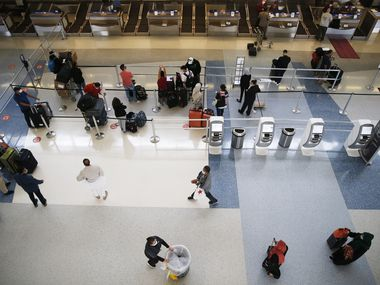 Travelers wait to check their bags in the Qatar Airways line of Terminal D at DFW International Airport on Monday.