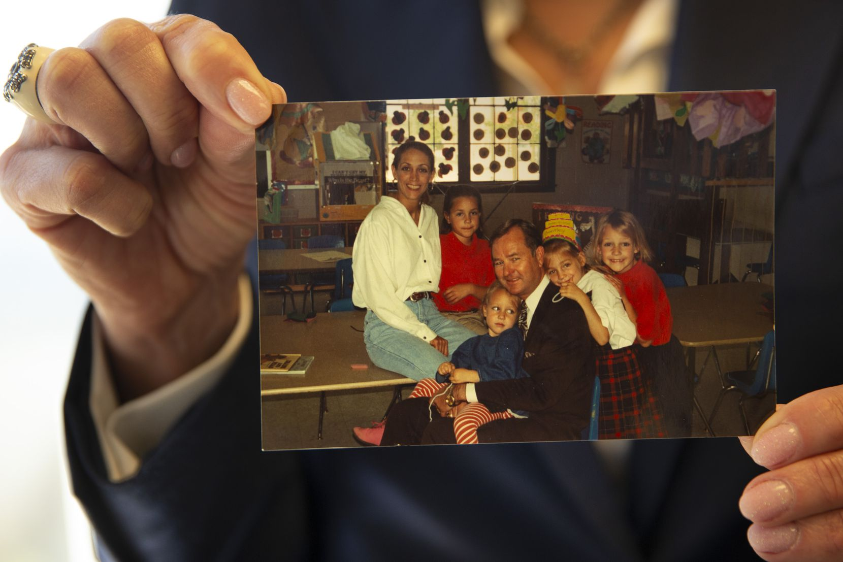 Terry Bentley Hill holds a family photograph from 1994 that includes all four of her daughters, including the youngest, Hallie, who is sitting in the lap of Hill's first husband, Danny. He died by suicide in 1995 while district attorney in Amarillo. Hallie died by suicide nine years later.