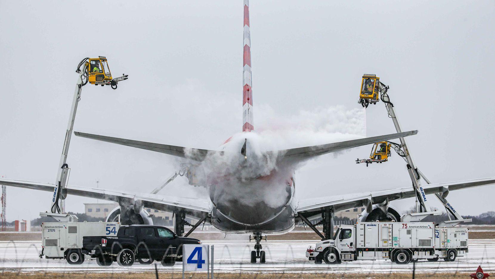 Una avión de American Airlines en el Aeropuerto Internacional DFW es rociado con químicos para quitarle el hielo antes de volar a temperaturas congelantes, el domingo 14 de febrero.