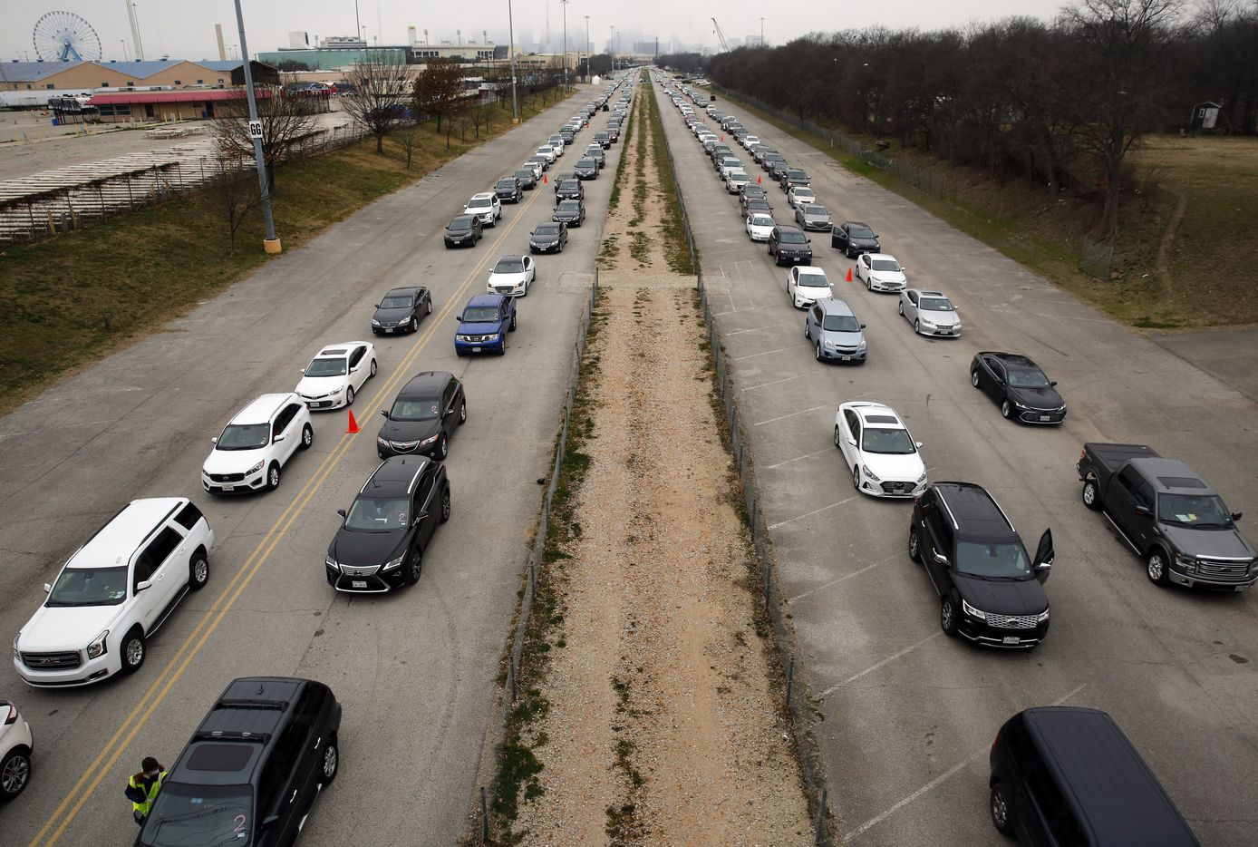 A long line of vehicles line up in Fair Park to receive COVID-19 vaccinations in Dallas, Wednesday, February 10, 2021. Dallas County's mega vaccine site shifted to a drive through model Wednesday, an effort to help move things quicker.  According to a press release, The White House announced today that it is partnering with the State of Texas to build three new major Community Vaccination Centers (CVCs) in Dallas, Arlington, and Houston. The CVCs will be at Fair Park in Dallas, AT&T Stadium in Arlington, and NRG Stadium in Houston.  Together, these sites will be capable of administering more than 10,000 shots in arms a day. (Tom Fox/The Dallas Morning News)