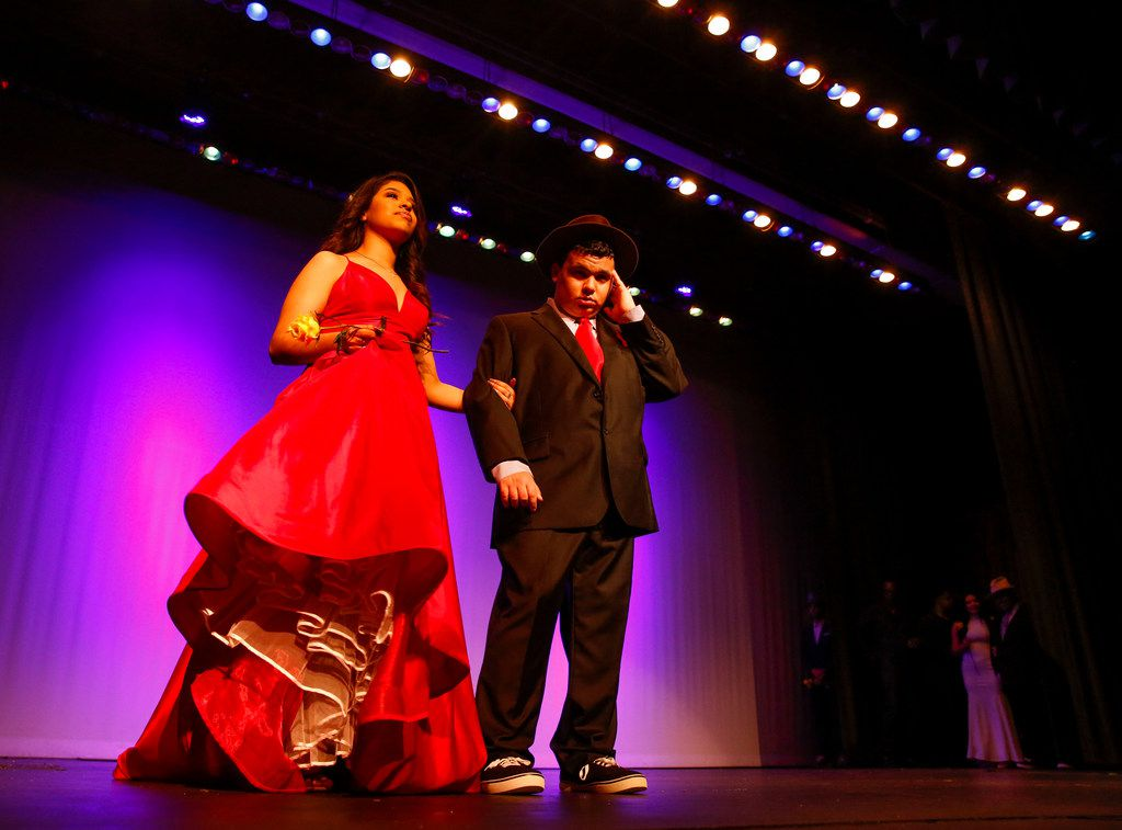Jennifer Gutierrez walks on stage with Jordan Negrete during a fashion show at Thomas Jefferson High School in Dallas on Wednesday, May 8, 2019. The Mark Cuban Heroes Basketball Center's Suit Up Experience provided custom made suits from Lombardo Custom Apparel for 10 young men.