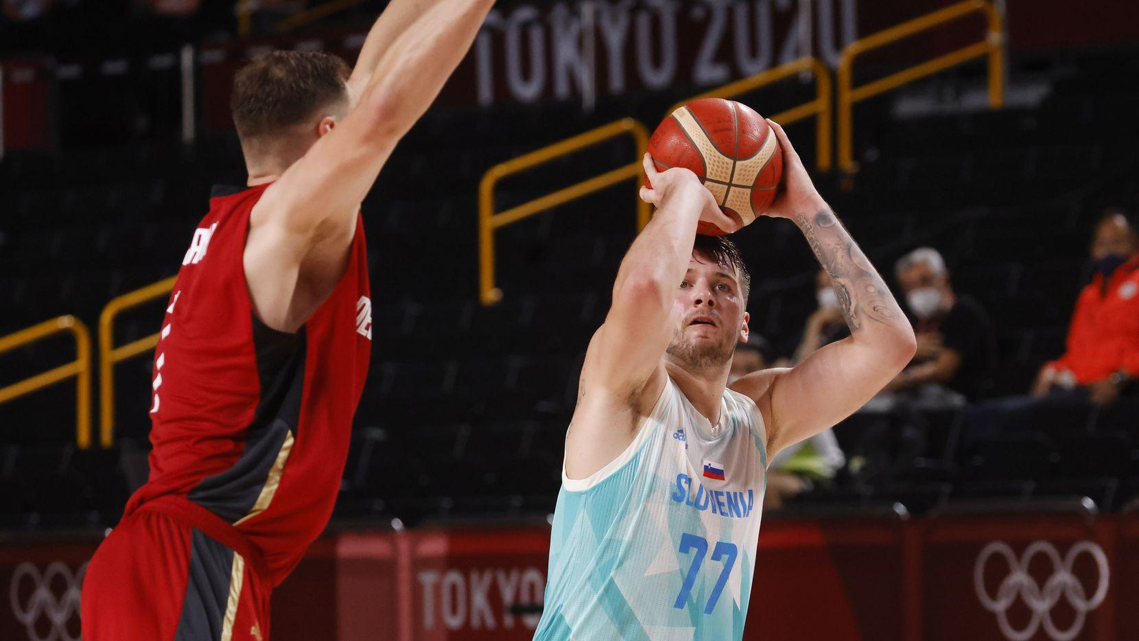 El esloveno Luka Doncic dispara por encima del alemán Johannes Thiemann durante el partido de cuartos de final varonil, el martes 3 de agosto de 2021, en Saitama, Japón.