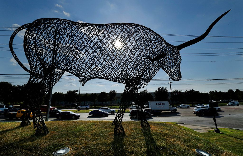 A large longhorn made out of steel looms over evening rush hour along Belt Line Road at Cypress Waters in Dallas.