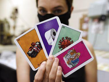 Alyssa Peña, directora de desarollo de negocios de Versa Printing, en Dallas, muestra algunas de las cartas de la Lotería Cuerentena, que idearon como una manera de sostener su negocio durante la pandemia.