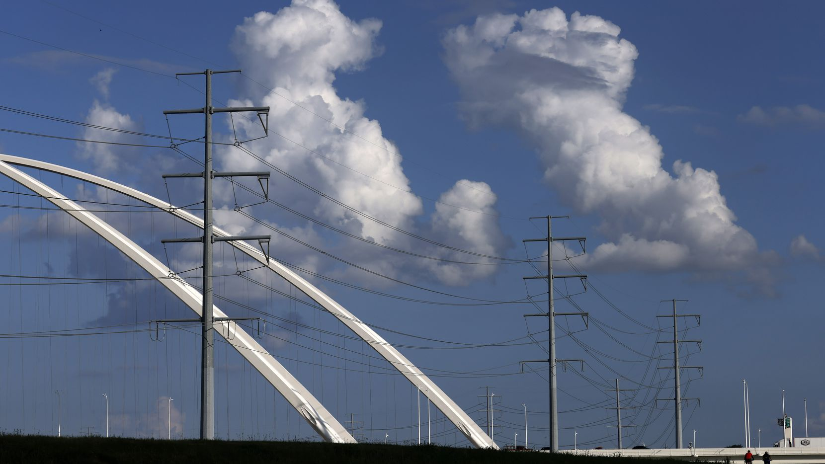 Large electrical transmissions lines are pictured along the Trinity River levee and Margaret McDermott Bridges near downtown Dallas, June 30, 2021.