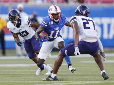 Southern Methodist Mustangs wide receiver Rashee Rice (11) attempts to evade Stephen F. Austin Lumberjacks safety JaTerious Evans (27) on a play during the first half of their home opener at Ford Stadium in Dallas, on Saturday, September 26, 2020.