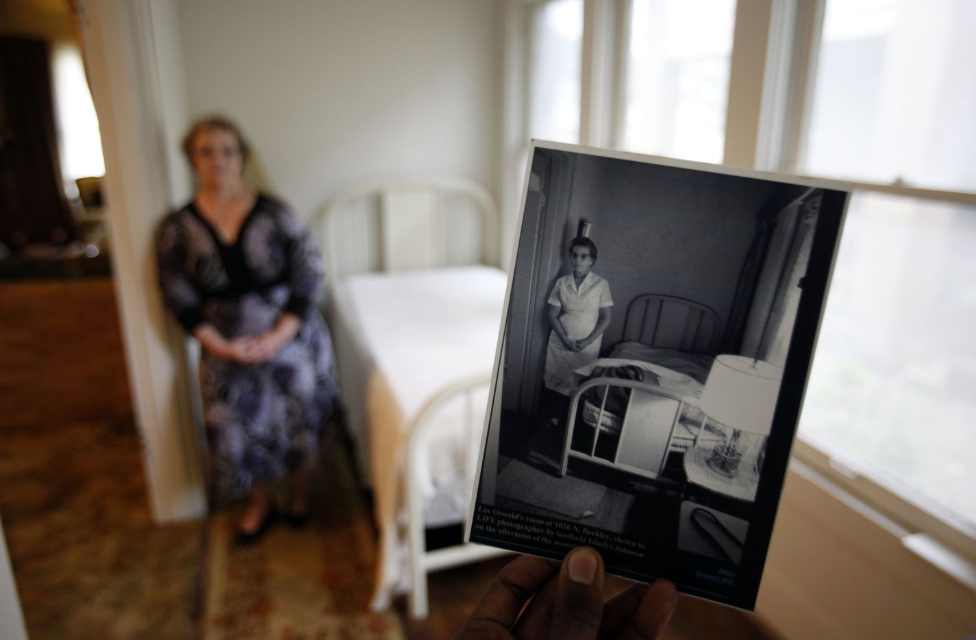 In the foreground is a photo of Pat Hall's grandmother, Gladys Johnson, taken by LIFE photographer Allan Grant the day of the assassination of Pres. John F. Kennedy. In 2013, Pat Hall stood next to the same bed in the same room at her house on N. Beckley Ave as the Dallas Morning News took her photo.
