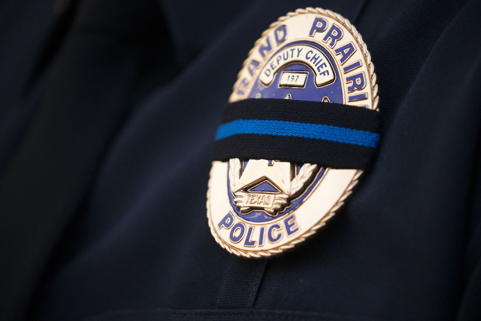 "A Grand Prairie police deputy chief's badge is covered with a mourning band in honor of Officer Albert ""A.J."" Castaneda during a vigil Sunday at the  Grand Prairie Public Safety Building. Castaneda was killed Friday when he fell from an overpass on the Bush Turnpike, where he was running radar outside his parked SUV when it was struck by another vehicle."