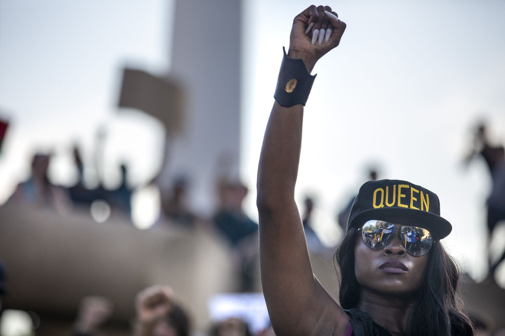 Jennifer Akabue raises her fist with other protesters as they participate in an 8-minute and 46-second kneel in honor of George Floyd during a demonstration at Dallas City Hall to denounce police brutality and systemic racism in Dallas on Thursday, June 4, 2020. The demonstration took place on the seventh consecutive day of organized protests in response to the recent deaths of George Floyd in Minneapolis and Breonna Taylor in Louisville.