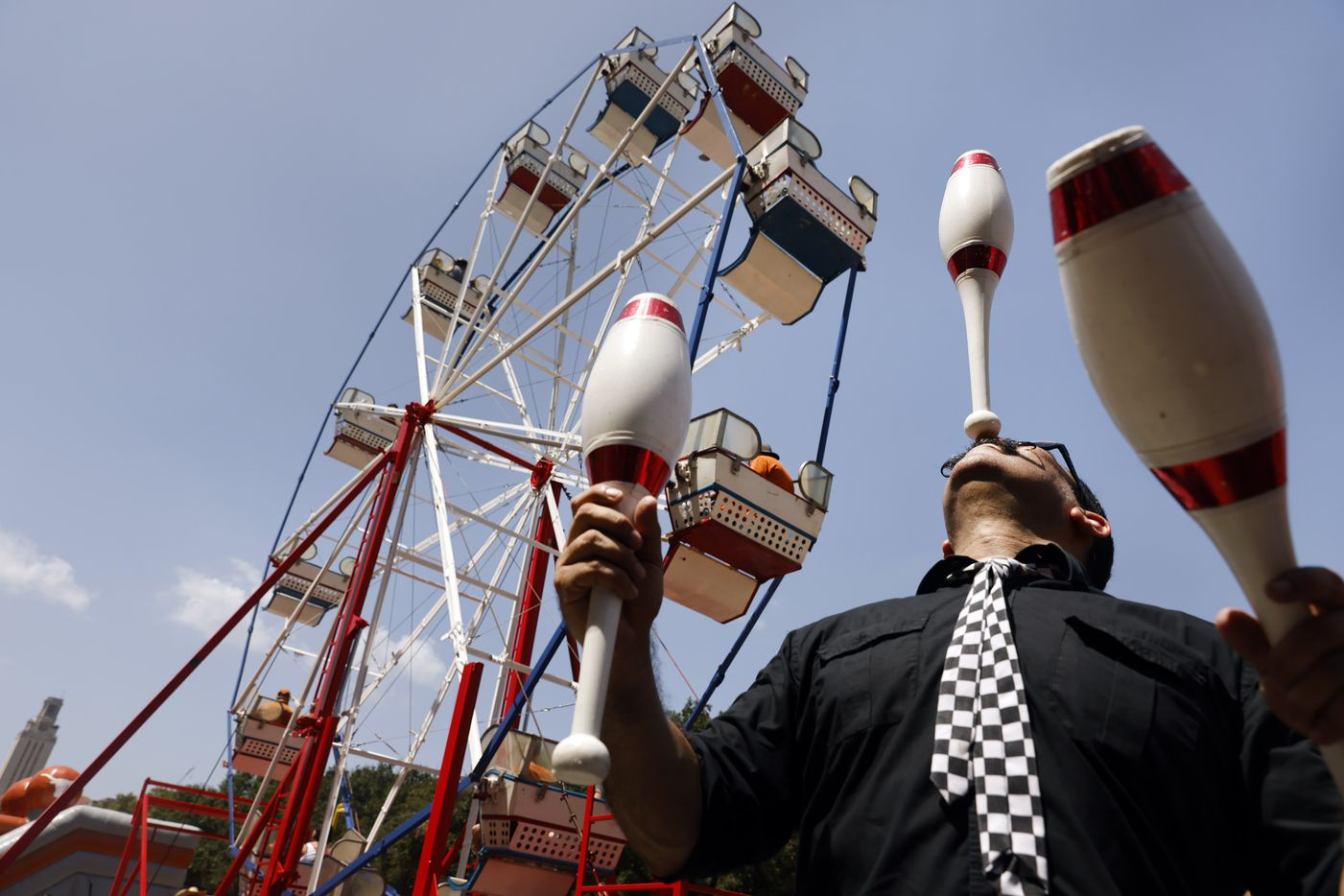 Circus performer Oscar Liendo juggles and glances bowling pins along Smokey's Midway outside of DKR-Texas Memorial Stadium in Austin, Saturday, September 4, 2021. The Longhorns were facing the Louisiana-Lafayette Ragin Cajuns. (Tom Fox/The Dallas Morning News)