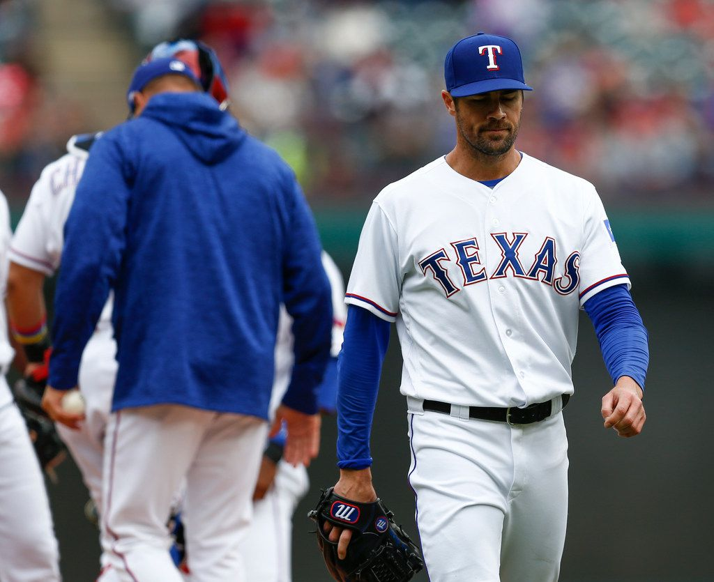 Texas Rangers starting pitcher Cole Hamels (35) leaves the game against the Toronto Blue Jays after he was relieved of his duties by manager Jeff Banister, left, during the sixth inning of a baseball game, Sunday, April 8, 2018, in Arlington, Texas. (AP Photo/Jim Cowsert)