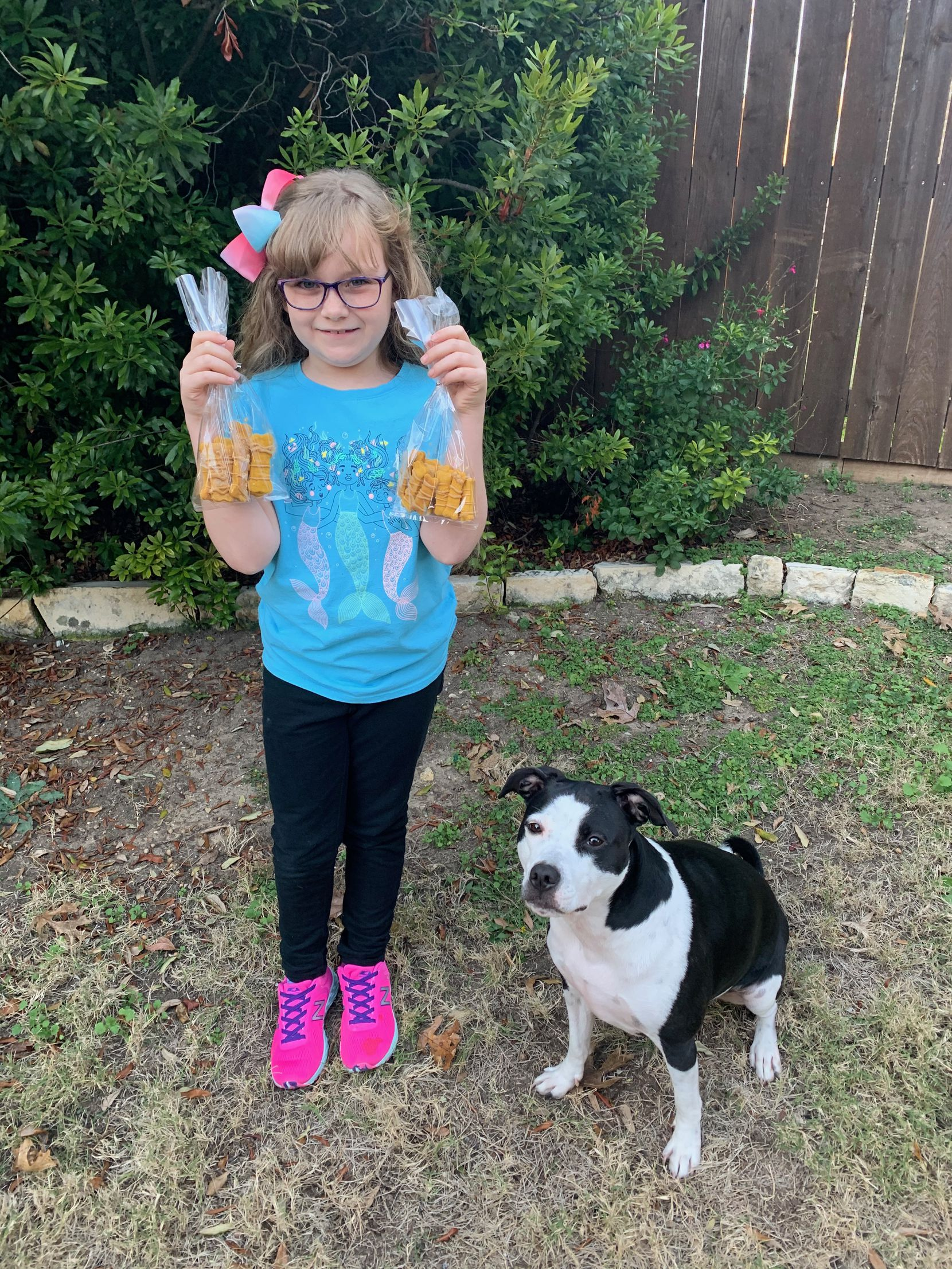Lily Romito, 8, and her 3-year-old Labrador mix Maggie with fresh homemade dog treats from Maggie's Barkery.