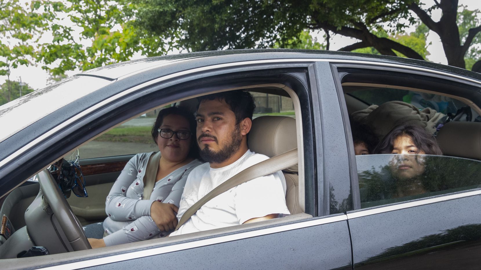 Carlos and Maria Sanchez pose for a portrait in their car at Holy Cross Catholic Church in South Dallas. The Sanchez family had just missed receiving food from a mobile food distribution organized by Catholic Charities. Since the beginning of the coronavirus pandemic, they have relied on the single income of Maria's father, who works at Subway.