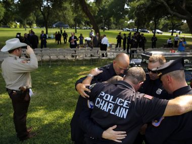 A police chaplain and officers from out of state pray following a graveside service for a slain Dallas officer in this 2016 file photo.