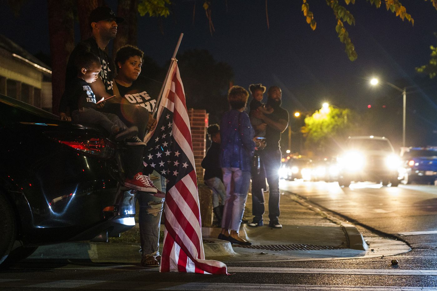 Protestors, including a man carrying an upside-down American flag, gathered outside the house where Atatiana Jefferson was shot and killed, during a community vigil for Jefferson on Sunday, Oct. 13, 2019, in Fort Worth.