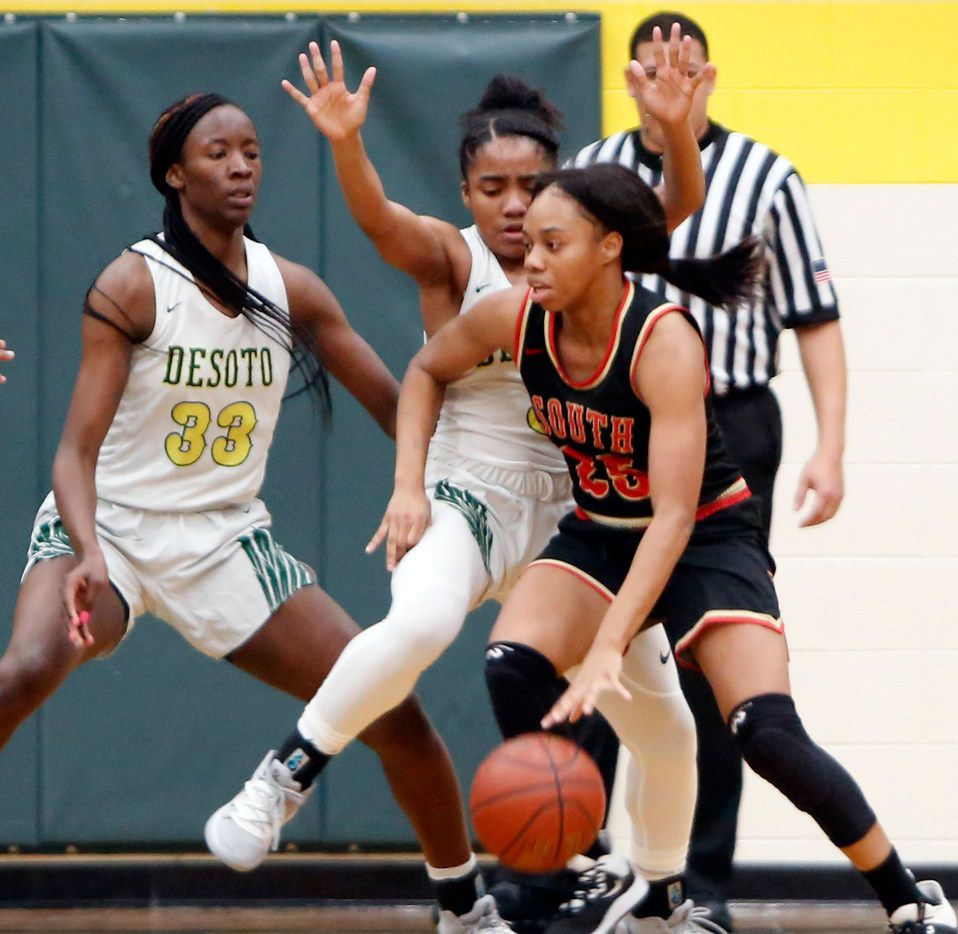 South Grand Prairie's Madison Jean-Louis (25) finds driving the ball challenging against the defense of DeSoto's Kayla Glover (3) and Amina Muhammad (33) during first half action. The two teams played their District 7-6A girls basketball game at DeSoto High School in DeSoto on January 21, 2020.