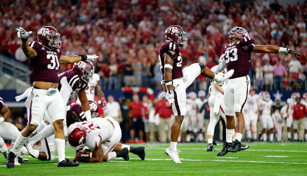 Texas A&M Aggies defenders from left Shaan Washington (33),  Armani Watts (23) and Claude George (31) celebrate their red zone stop of Arkansas Razorbacks running back Kody Walker (24) in the second quarter of the Southwest Classic at AT&T Stadium in Arlington, Texas, Saturday, September 24, 2016.(Tom Fox/The Dallas Morning News)