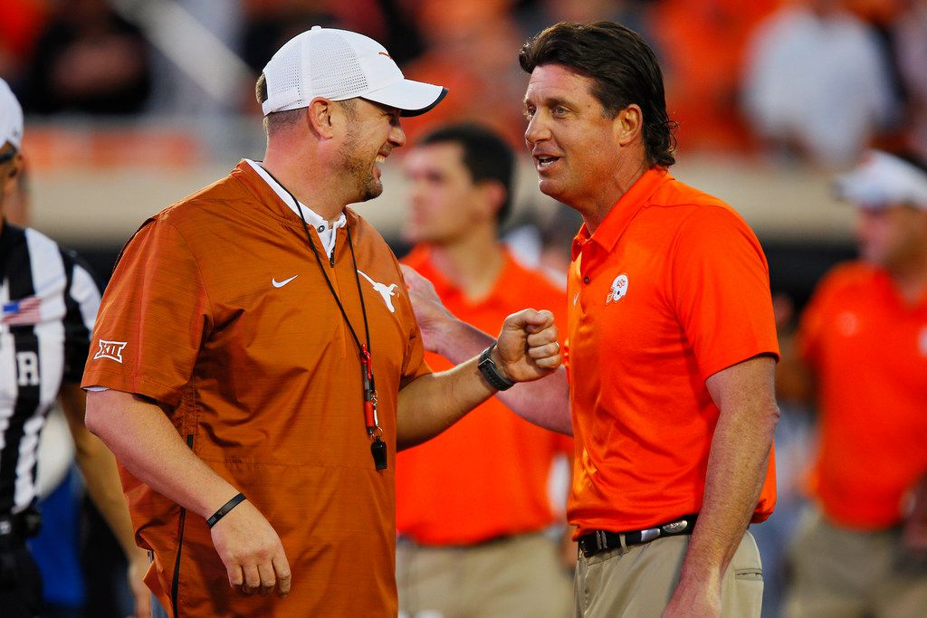 STILLWATER, OK - OCTOBER 27:  Head coach Tom Herman of the Texas Longhorns greets head coach Mike Gundy of the Oklahoma State Cowboys before their game on October 27, 2018 at Boone Pickens Stadium in Stillwater, Oklahoma.  (Photo by Brian Bahr/Getty Images)