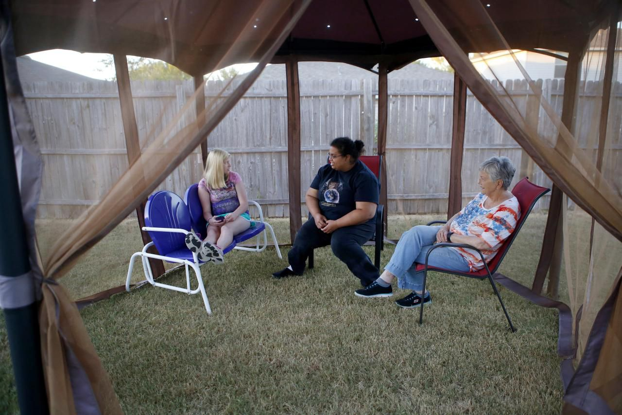 Shayna Forrest (center), who has a learning disability, enjoys the backyard of the McKinney home she shares with Samantha Russell (left) during a visit with service provider Judy Canterbury.