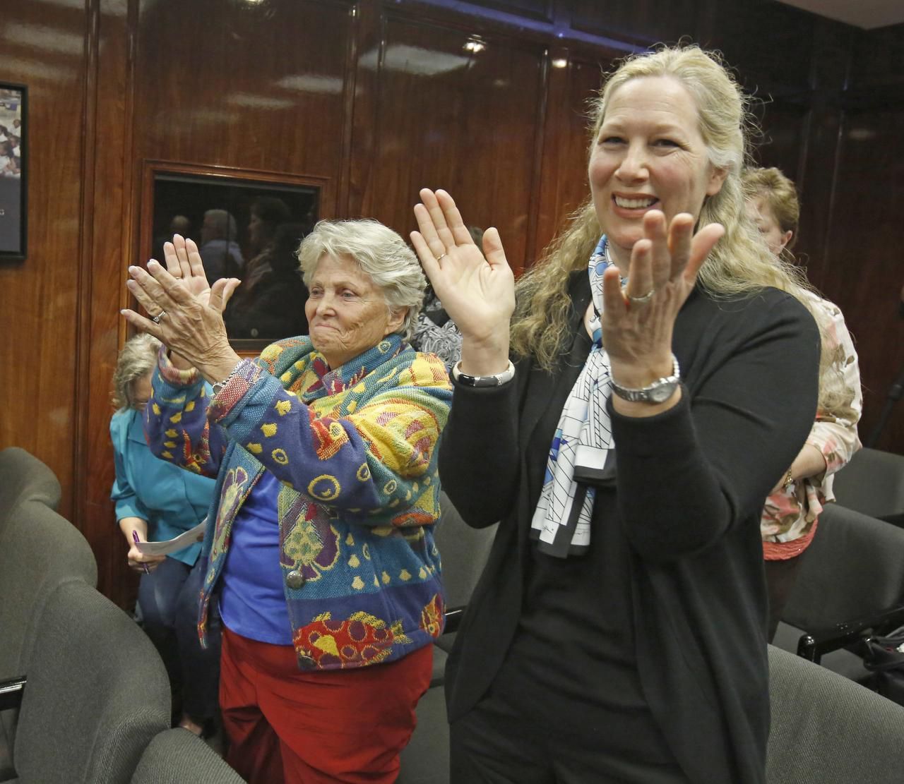 Retired state Rep. Harryette Ehrhardt (left) and Kyle Renard cheered after the Dallas ISD commission voted Tuesday not to create a home-rule charter.