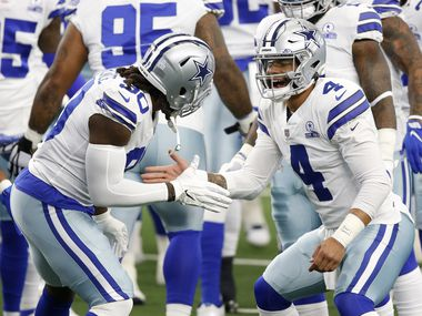 Dallas Cowboys quarterback Dak Prescott (4) greets Dallas Cowboys defensive end DeMarcus Lawrence (90) during warmups before a game against the Cleveland Browns at AT&T Stadium in Arlington, Texas on Saturday, October 4, 2020.