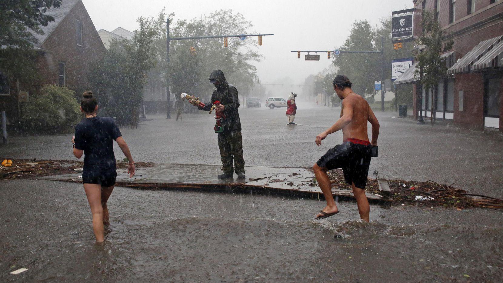 Personas camina en medio de una calle en New Bern en Carolina del Norte el viernes por la mañana.(AP)